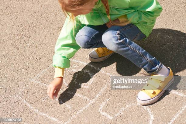 high angle view of little schoolgirl drawing hopscotch pattern on asphalt with chalk for playing - school girl shoes stock pictures, royalty-free photos & images