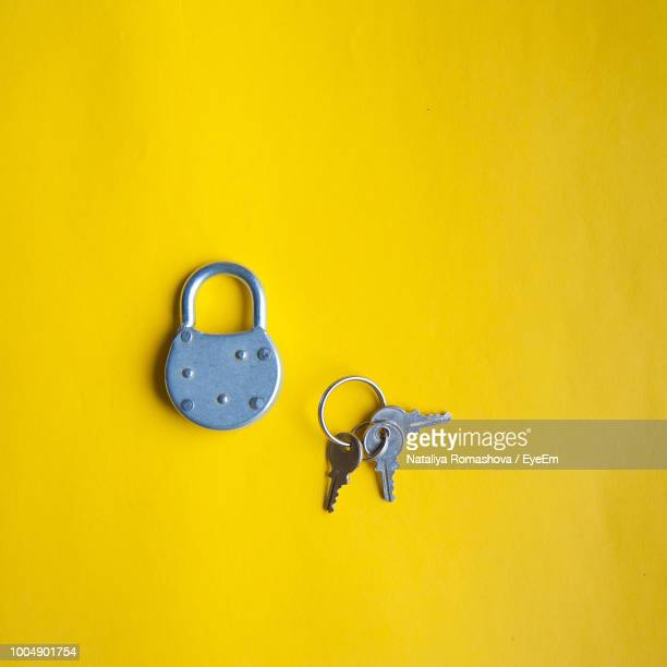 High Angle View Of Lock With Keys Over Yellow Background