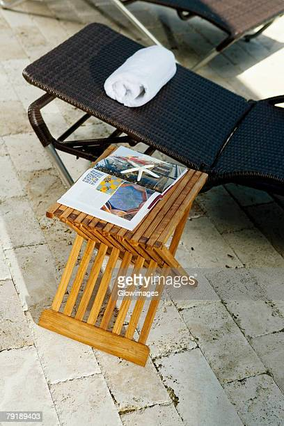 High angle view of lounge chairs and a table at the poolside