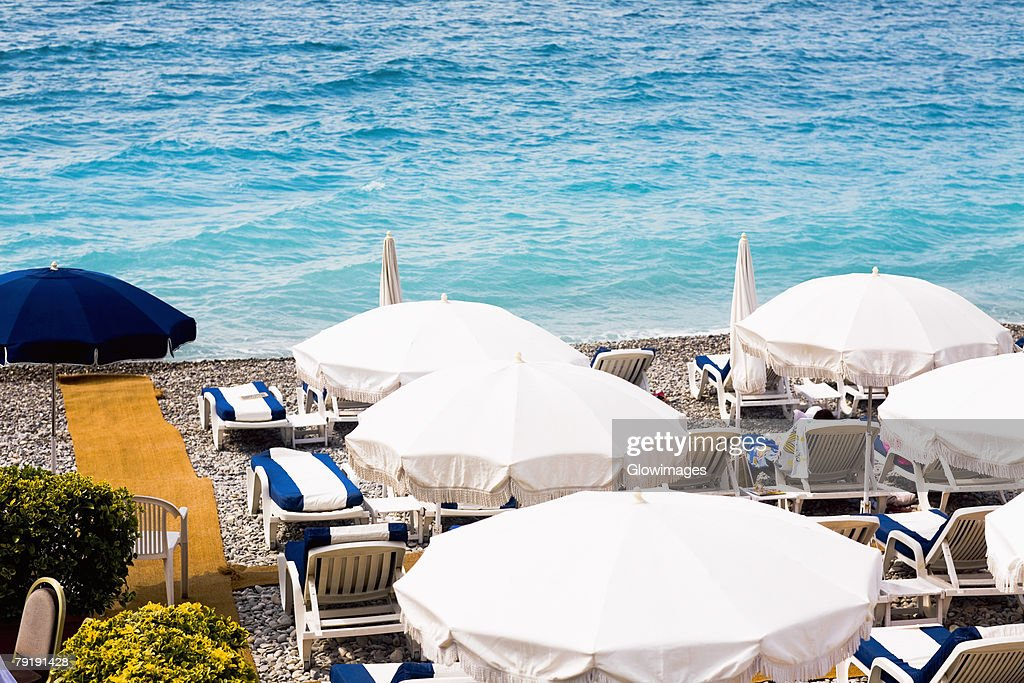 High angle view of lounge chairs and beach umbrellas on the beach, Nice, France : Stock Photo