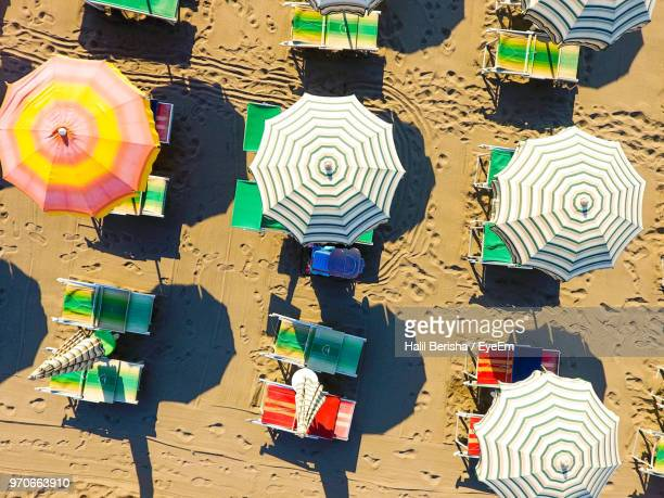 high angle view of lounge chairs and parasols at beach - parasol stock pictures, royalty-free photos & images