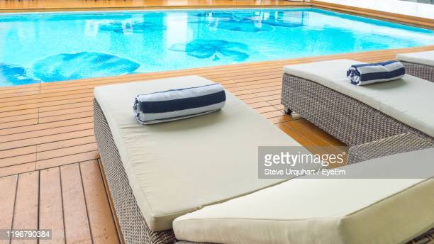 high angle view of lounge chairs by swimming pool - sun lounger stock pictures, royalty-free photos & images