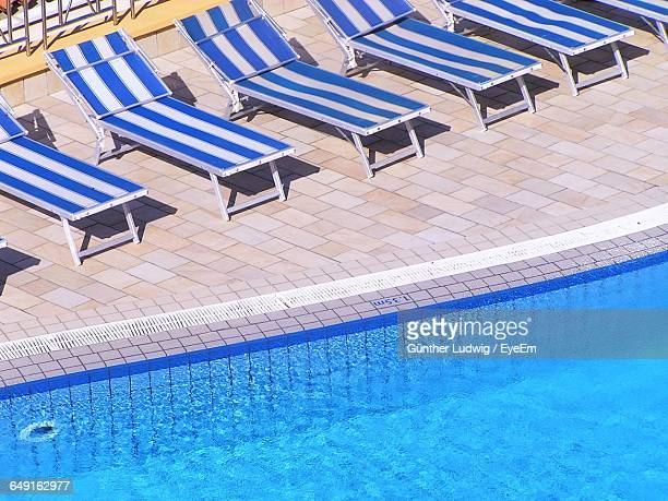 High Angle View Of Lounge Chairs By Swimming Pool