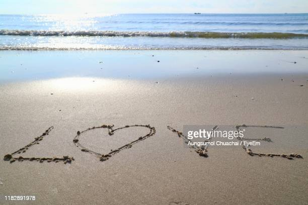 high angle view of love text on beach - aungsumol stock pictures, royalty-free photos & images