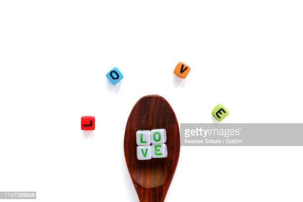 high angle view of love text on beads by wooden spoon against white background - perlenschnur stock-fotos und bilder