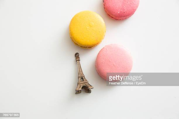 high angle view of macaroons and eiffel tower figurine over white background - macarons stock photos and pictures