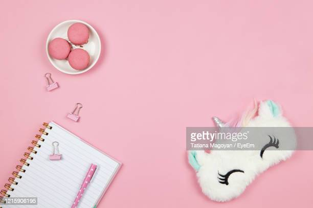 high angle view of macaroons with book and purse on pink background - pink purse stock pictures, royalty-free photos & images