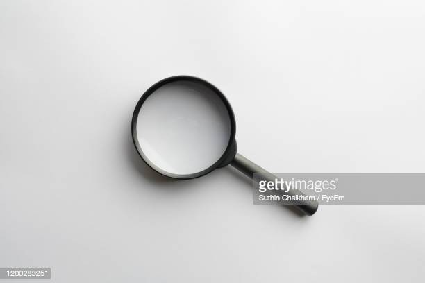 high angle view of magnifying glass against white background - 虫メガネ ストックフォトと画像