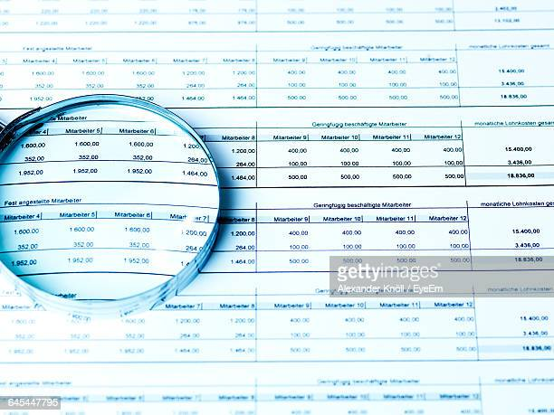 High Angle View Of Magnifying Glass On Document In Office