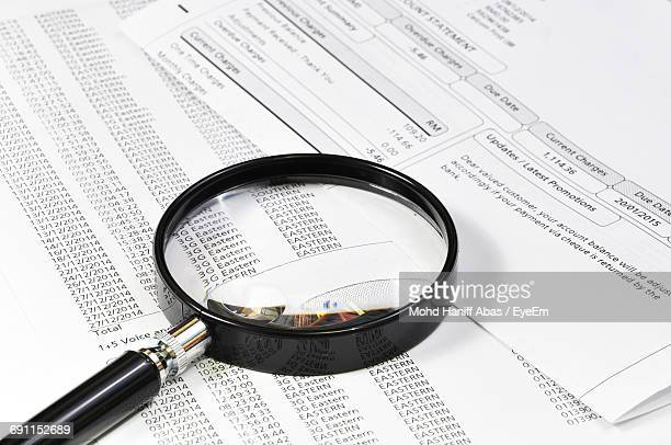 High Angle View Of Magnifying Glass On Documents