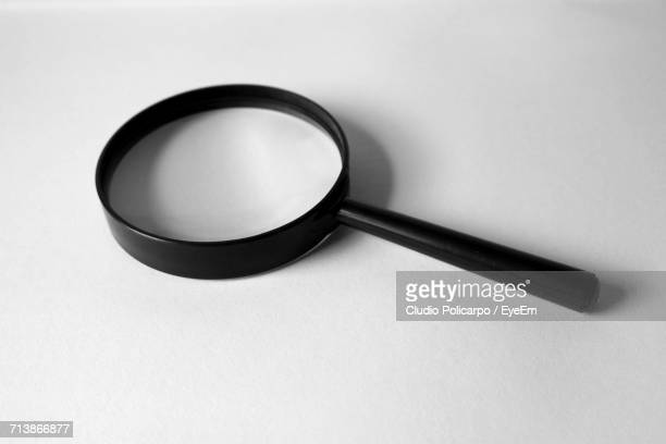 High Angle View Of Magnifying Glass On White Background