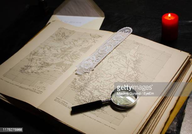 high angle view of magnifying glass on world map - geografia fisica foto e immagini stock