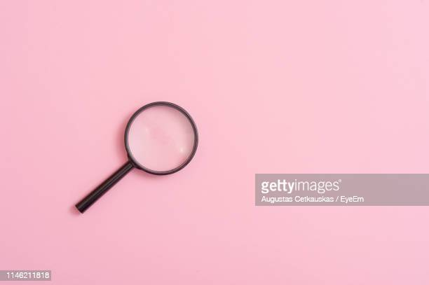 high angle view of magnifying glass over pink background - magnifying glass stock pictures, royalty-free photos & images