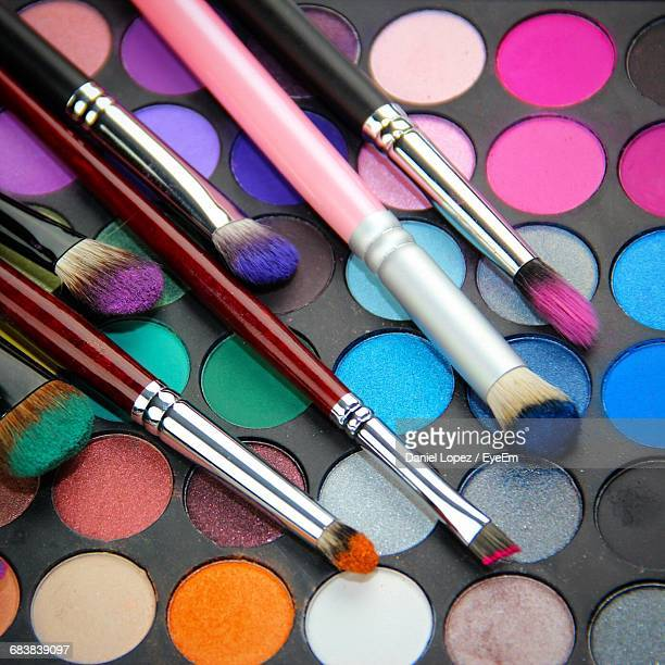 High Angle View Of Make-Up Brushes On Colorful Eyeshadow Palette