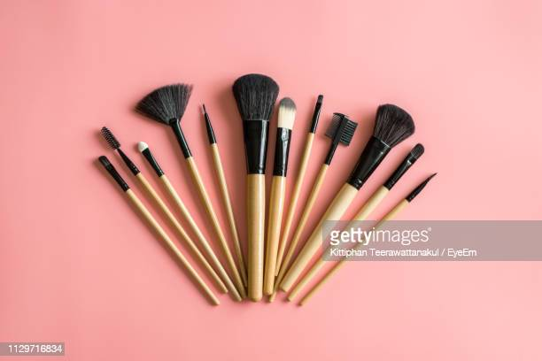 high angle view of make-up brushes on peach background - メイクアップブラシ ストックフォトと画像