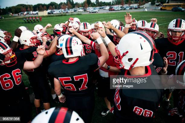 high angle view of male american football team cheering on field - high school football stock pictures, royalty-free photos & images