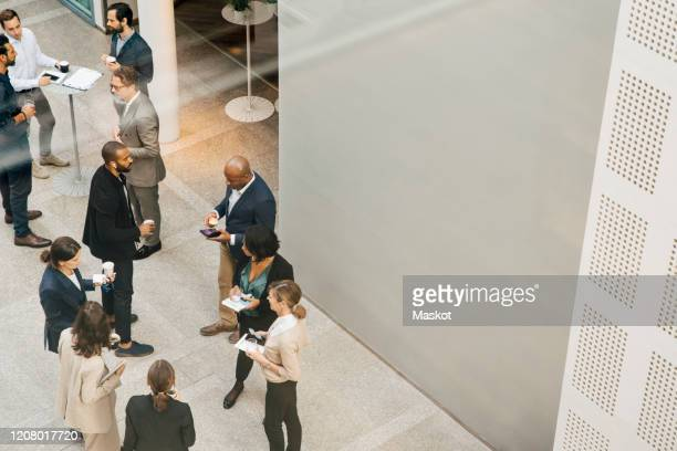 high angle view of male and female entrepreneurs talking outside office - formal businesswear stock pictures, royalty-free photos & images