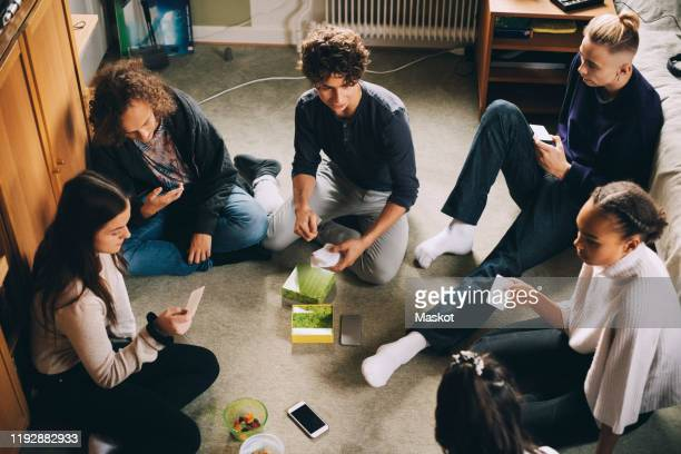 high angle view of male and female friends playing board game while sitting in bedroom at home - teenagers only stock pictures, royalty-free photos & images