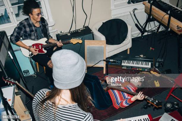 high angle view of male and female friends playing guitars while rehearsing in studio - rehearsal stock pictures, royalty-free photos & images