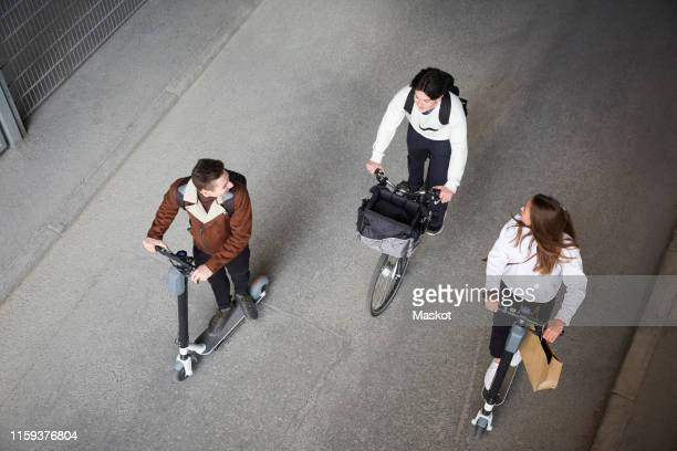 high angle view of male and female friends riding electric push scooters and bicycle on road in city - electric scooter stock pictures, royalty-free photos & images