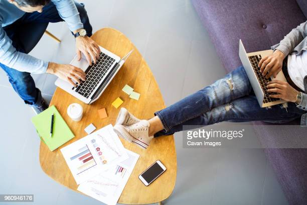 high angle view of male coworkers working in office - unterer teil stock-fotos und bilder