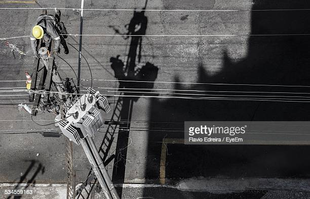 high angle view of male electrician working on top of electricity pylon - isolated color stock pictures, royalty-free photos & images