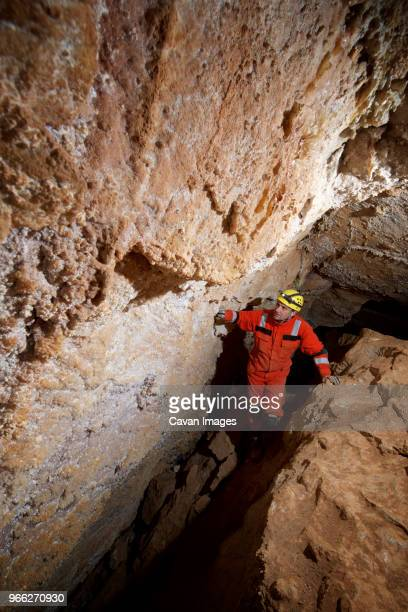high angle view of male hiker spelunking cave - speleology stock pictures, royalty-free photos & images