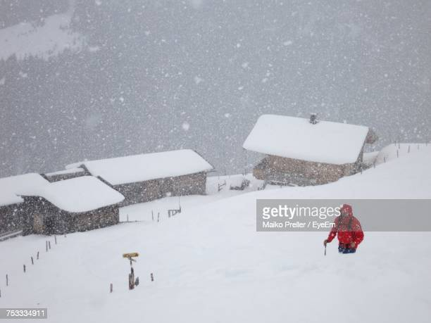 High Angle View Of Male Hiker Walking On Snow Covered Field