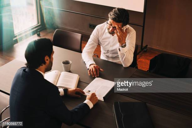 high angle view of male lawyer showing file to mature stressed client at board room in law office - law stock pictures, royalty-free photos & images