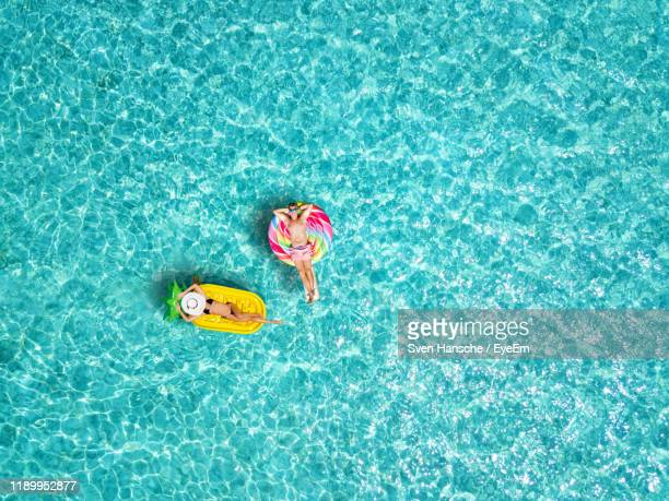 high angle view of man and woman relaxing on inflatable raft in swimming pool - tropical climate stock pictures, royalty-free photos & images