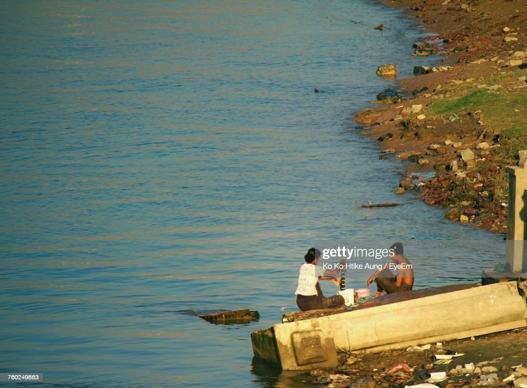 High Angle View Of Man And Woman Sitting On Jetty At Seashore : Stock Photo