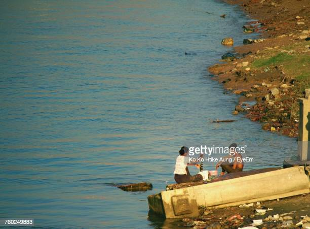high angle view of man and woman sitting on jetty at seashore - ko ko htike aung stock pictures, royalty-free photos & images