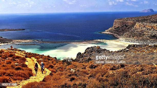 high angle view of man and woman walking on pathway against sea - creta fotografías e imágenes de stock