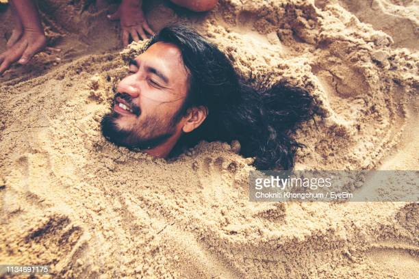 high angle view of man buried in sand at beach - 埋まる ストックフォトと画像