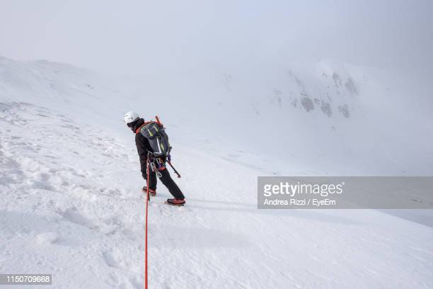 high angle view of man climbing snow covered mountain - andrea rizzi stockfoto's en -beelden