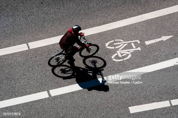 high angle view of man cycling on bicycle lane during sunny day - solo un uomo foto e immagini stock