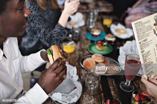 High angle view of man eating burger while sitting with female friends at restaurant