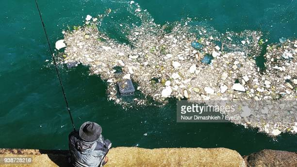 High Angle View Of Man Fishing In Contaminated Sea