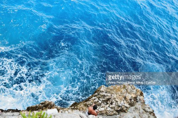 high angle view of man fishing in sea while standing on rock formation - anna fischer stock-fotos und bilder