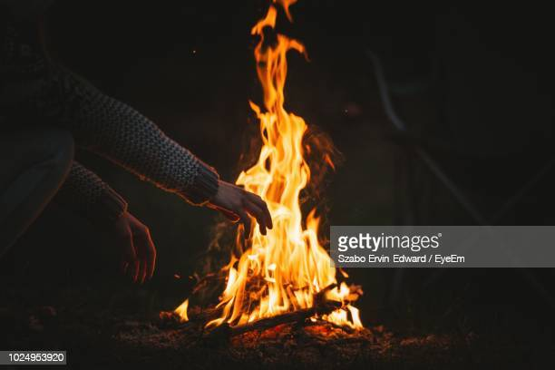 high angle view of man gesturing against campfire - lagerfeuer stock-fotos und bilder