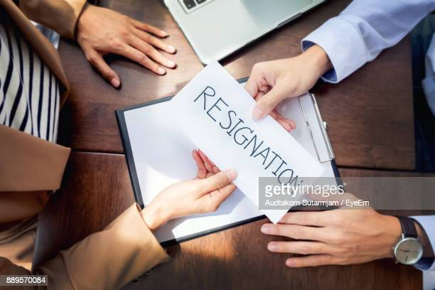 high angle view of man giving resignation letter to businesswoman at office - quitting a job stock pictures, royalty-free photos & images