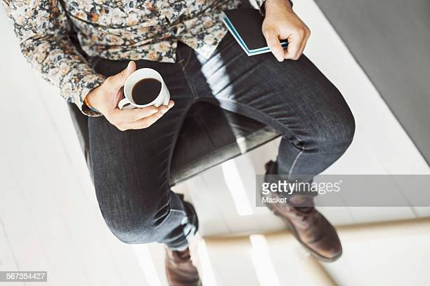 High angle view of man holding coffee cup and note pad at home office