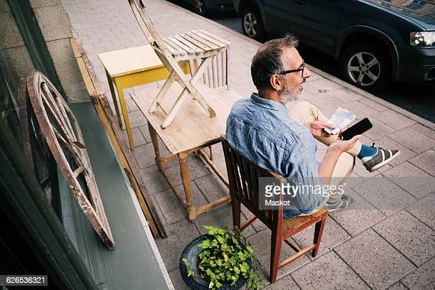 High angle view of man holding mobile phone while sitting outside antique shop