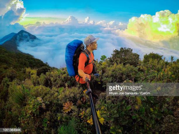 High Angle View Of Man Holding Monopod While Standing Amidst Plants On Mountain