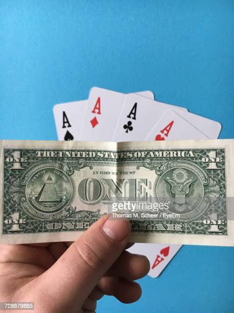 High Angle View Of Man Holding Paper Currency Against Aces Cards