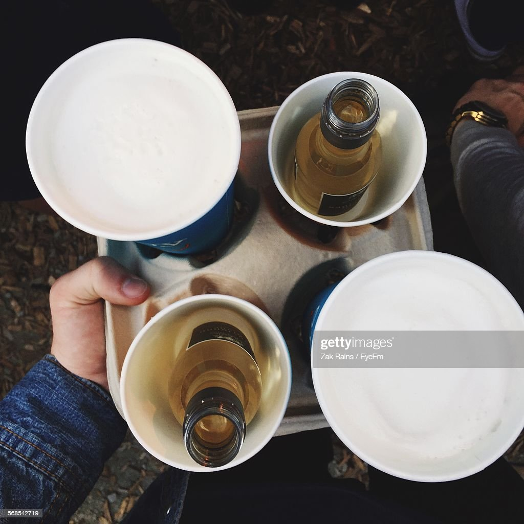 High Angle View Of Man Holding Tray With Bottles And Cups In It : Stock Photo