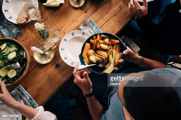 High angle view of man holding utensil of potatoes and carrots while sitting with friends