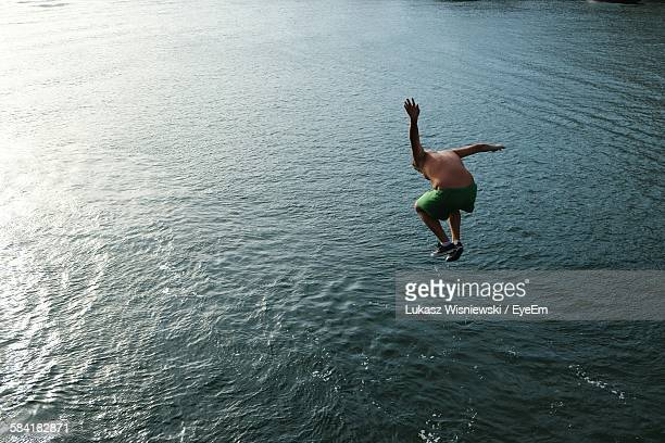 High Angle View Of Man Jumping In Lake
