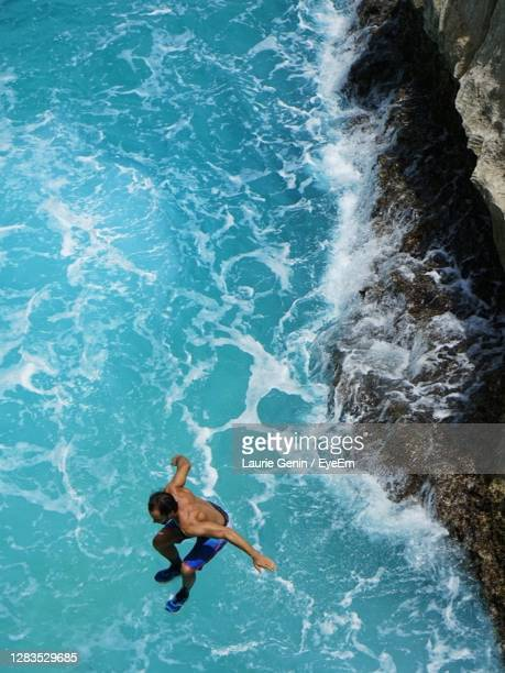 high angle view of man jumping in sea - antigua & barbuda stock pictures, royalty-free photos & images