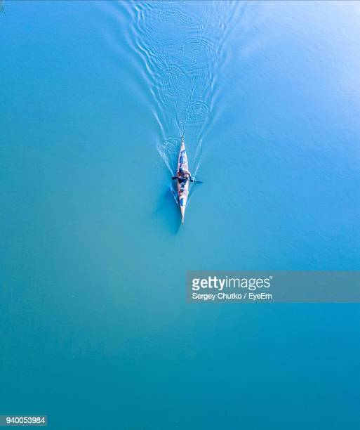 high angle view of man kayaking on lake - kajak stock-fotos und bilder